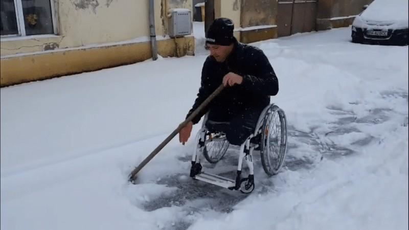 Imagini emoționante cu un bărbat în scaun cu rotile care deszăpezește trotuarul din fața casei-VIDEO